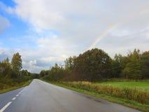 路、树和美丽的多云天空 免版税库存照片