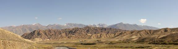 路全景通过农村Kyrgyzs的储河谷峡谷 库存照片