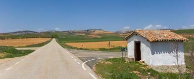 路和一点白色房子卡斯蒂利亚y利昂的风景的 库存照片