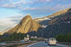 路和城堡看法有汽车的在瑞士在冬天 免版税库存图片