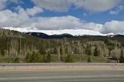 路和多雪的山在背景中 免版税库存照片