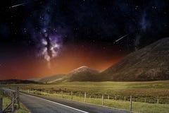 路和山夜风景在空间 免版税库存图片