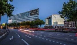 路和现代玻璃大厦在夜之前 免版税图库摄影