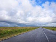 路和美丽的多云天空,立陶宛 免版税库存图片