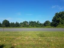 路和被割的草与金属岗位和绳索篱芭在路一边 免版税库存图片