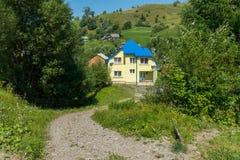 路在乡下撒布与导致下来两个地板的房子的石渣与一个铺磁砖的屋顶和两 免版税库存照片
