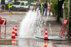 路在交通锥体旁边的喷射水 库存图片