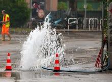 路在交通锥体旁边的喷射水 免版税库存照片
