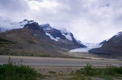 路在加拿大罗基斯,有雪山、蓝色钥匙和云彩的在背景中 免版税库存图片