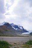 路在加拿大罗基斯,有雪山、蓝色钥匙和云彩的在背景中 免版税库存照片