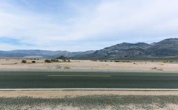路在有多云天空和镶边山的莫哈韦沙漠 图库摄影