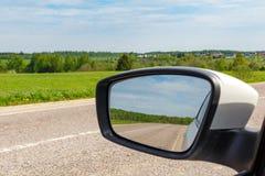路在汽车旁边镜子反射了在一个晴天 汽车城市概念都伯林映射小的旅行 免版税库存照片