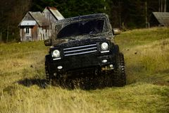 路在黑颜色的汽车在赛跑参与 越野召集或在乡下小屋在旁边森林附近的集会袭击 免版税库存照片