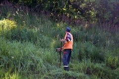 路工作者割在路旁的草在古板手工割 免版税库存照片