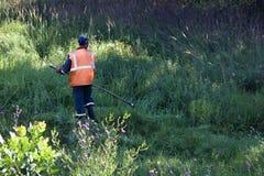 路工作者割在路旁的草在古板手工割 库存照片