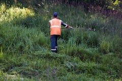 路工作者割在路旁的草在古板手工割 图库摄影