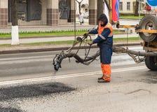 路工作者投入热的沥青修理在路的坑在普斯克夫,俄罗斯的中心 免版税库存图片