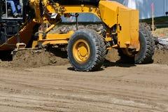 路平地机成水平在修路项目的沙子 库存图片