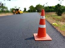 路建设中并且有在路的一个红色橡胶锥体 免版税库存图片