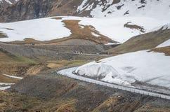 路弯在大山的 在背景的雪 免版税图库摄影