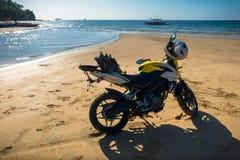 路摩托车和盔甲在热带海滩停放了 免版税库存照片