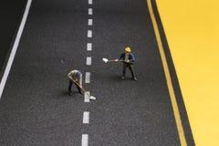 路整修过程中的宏观小雕象 免版税库存照片