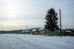 路旁小西伯利亚村庄,在冬天季节的晚上 库存图片