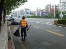 路旁撤除的卫生工作者除草 免版税库存照片