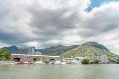 路易港,毛里求斯- 2015年10月01日:口岸和海洋在路易港, Mautirius浇灌 多云天空和建筑学在backgroun 免版税库存照片