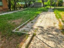 路是一条石道路进入一栋居民住房的庭院,有开花的树的一个围场和绿草 图库摄影