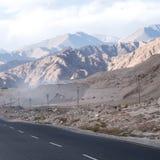 路有山景和蓝天背景 免版税库存图片