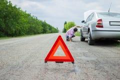路标、紧急状态和交通概念-在残破的汽车的警告的三角 库存图片