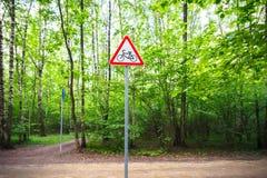 路标警告关于木头的骑自行车者 免版税库存照片