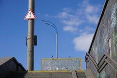 路标-在垂悬在杆的一个红色三角的黑感叹号,警告关于危险 免版税库存图片