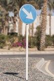 路标`改道对在路的正确的`在度假区,在与棕榈树的一天在背景中 库存照片
