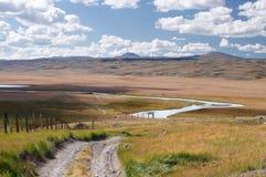 路沿着在高地山高原的边界线与在谷怀特河的背景的绿草 免版税库存图片