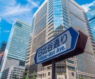 路牌和现代办公楼在东京街市-东京,日本- 2018年6月19日 免版税库存照片