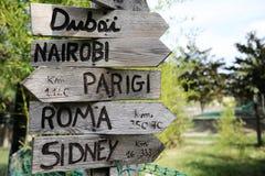 路牌表明方向的自然公园对世界的不同的地方 背景的绿色植物 免版税库存图片