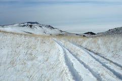 路的冒险 在沙漠开汽车通过深雪被放置的路 雾房子横向早晨剪影结构树 库存图片