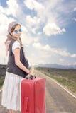 路的女孩带着葡萄酒衣裳和手提箱 免版税图库摄影