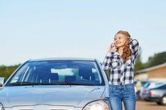 路的妇女在一辆残破的汽车附近要求帮助 免版税库存照片