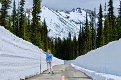 路的妇女有雪墙壁的 免版税图库摄影