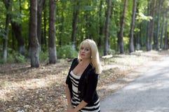 路的美丽的金发碧眼的女人在公园 免版税库存图片