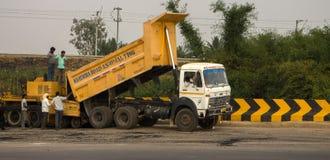 路的道路工程和建筑在印度 翻斗车卸载沥青入asphalter摊铺机,蒸汽路辗, 图库摄影