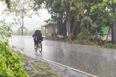 路的骑自行车者在雨中 免版税图库摄影