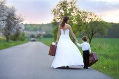 路的年轻新娘带着手提箱 库存照片
