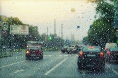路的Vew通过汽车的挡风玻璃有雨珠的 风暴,恶劣天气 库存照片