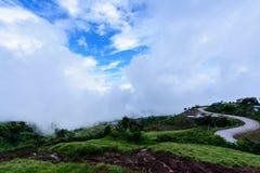 路线在与早晨雾的蓝天下在山景 免版税库存图片