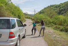 路自动停止的游人 远足棍子临近我-搭车 图库摄影