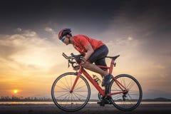 路自行车骑自行车者人循环 骑自行车炫耀健身运动员在一条开放路的骑马自行车对日落 免版税库存照片